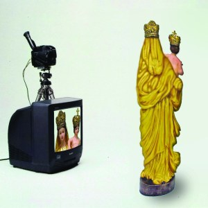 """TV Our Lady of Prompt Succor (Nam June Paik)"" – IRL, Nam has his ""TV Buddha,"" which definitely has a better ring to it. But in bizarro-Louisiana art history world, Our Lady of Prompt Succor reigns supreme across the art airwaves. She's gold and shiny and the freakin' MOTHER OF GOD! See … she's holding lil' Baby Jesus in her arms. We in Louisiana love lil' Baby Jesus so much we bake little plastic versions of him in our Mardi Gras King Cakes, risking death by asphyxiation if we accidentally swallow him. Whoever finds and survives the ordeal of King Cake consumption is indebted to buy the next king cake and continue to the next round of King Cake death matches leading up to Fat Tuesday. But I digress … Our Lady of Prompt Succor is there for you whether you die from lil' Baby Jesus asphyxiation, diabetes and heart disease attributed to sugary, seasonal coffee cakes from Louisiana, or just plain old natural causes like Corexit poisoning. She's always there to succor you … and she's prompt. She's got better things to do than sit on a giant lotus blossom under a tree while staring at her navel, contemplating the essential emptiness of the universe."